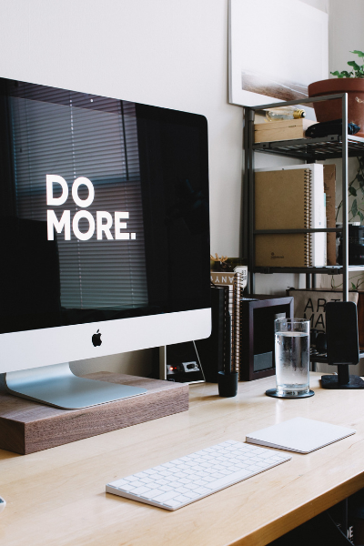 """Picture of an iMac desktop workspace with the words """"Do More"""" on the monitor"""