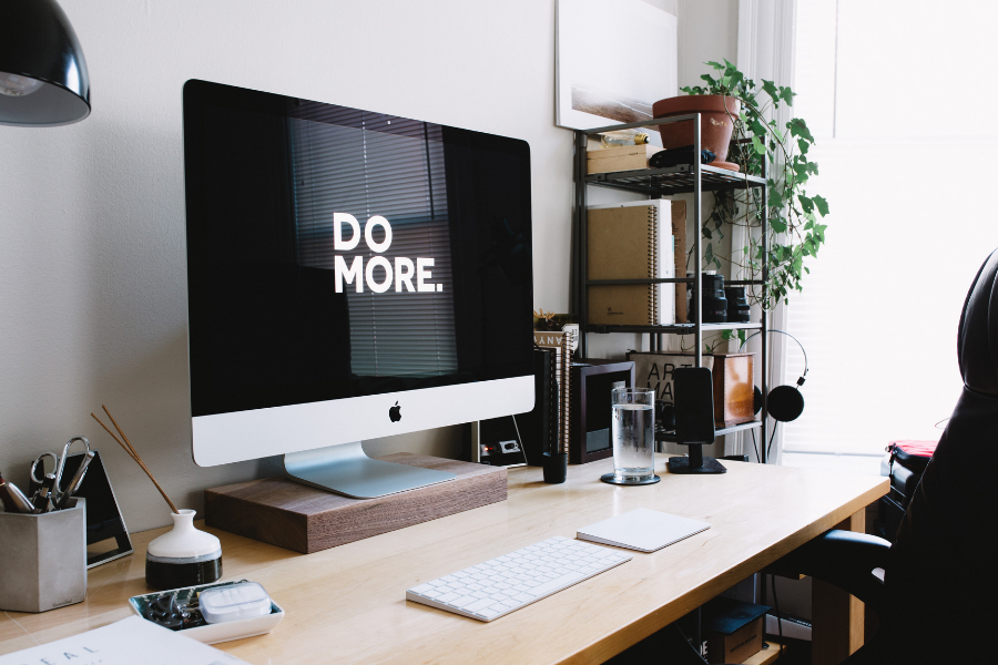 "Picture of an iMac desktop workspace with the words ""Do More"" on the monitor"