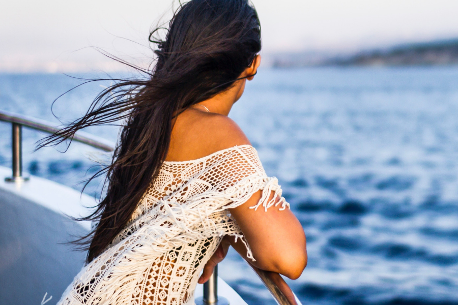 Image of a woman on a ship looking out onto the ocean