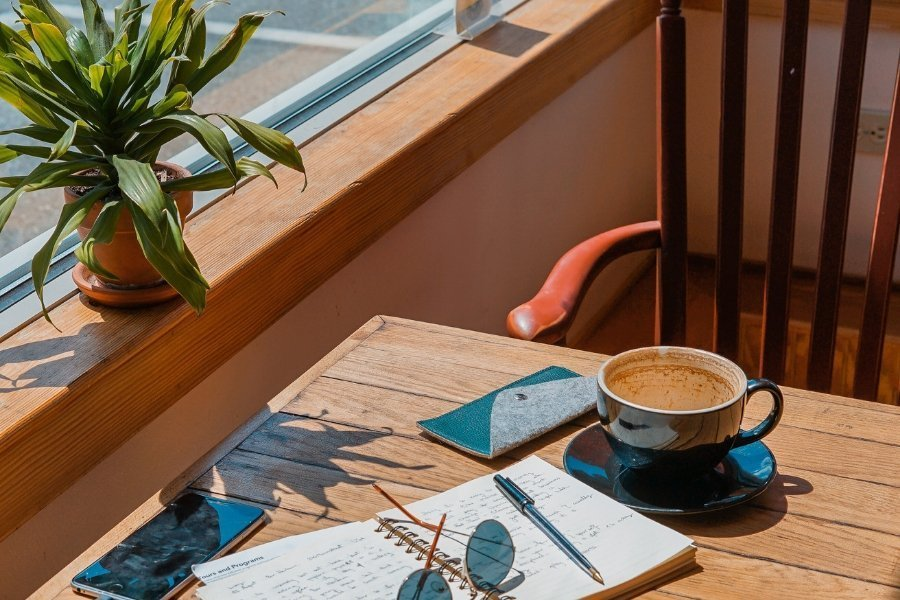 Picture of a table in a cafe with a journal, sunglasses, and a coffee