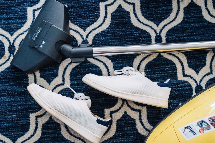 Picture of a vacuum cleaner on a rug with white sneakers